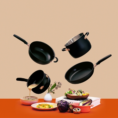 Meyer Accent series frying pans and pots floating above a orange color dining table decorated with food
